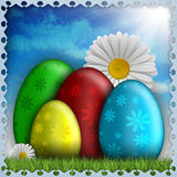 Spring flowers and colored eggs on blue background Stock Photo