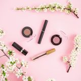 Spring flowers with cosmetics isolated on pink background. Flat lay, top view. Spring time stock photography