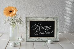 Spring flowers, Easter decorations and a blackboard on white tab. Le. Text `Happy Easter` on the board Royalty Free Stock Image