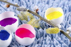 Spring flowers and Easter egg shells filled with colorful paints Royalty Free Stock Images