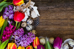 Spring flowers with easter eggs. Easter frame with fresh flowers, eggs and rabbits close up with copy space on wooden desktop Royalty Free Stock Photography