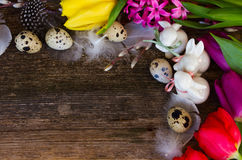 Spring flowers with easter eggs. Spring easter frame with fresh flowers, eggs and rabbits close up with copy space on wooden desktop background Stock Photos