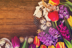 Spring flowers with easter eggs. Easter frame with fresh flowers, eggs and rabbits close up with copy space on wooden desktop, retro toned Stock Image