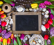 Spring flowers with easter eggs. Spring easter frame with fresh flowers, eggs and rabbits on textured wooden table with copy space on blackboard Stock Photos
