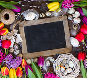 Spring flowers with easter eggs. Spring easter frame with fresh flowers, eggs and rabbits on textured wooden table with copy space on empty blackboard Royalty Free Stock Images
