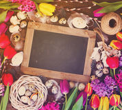 Spring flowers with easter eggs. Spring easter frame with fresh flowers, eggs and rabbits on textured wooden table with copy space on empty blackboard, retro Royalty Free Stock Images