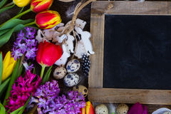 Spring flowers with easter eggs. Spring easter frame with fresh flowers, eggs and wooden rabbits close up with copy space on blackboard Royalty Free Stock Image