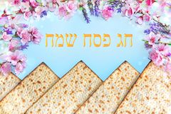 Spring flowers and matzah. Machine-made matzot from Jerusalem and spring flowers, inscription in hebrew - Happy Passover stock photos