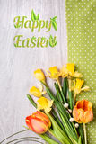Spring flowers on napkinon wood, Happy Easter caption Stock Photos
