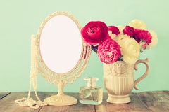 Spring flowers, perfume bottle and pearls next to blank vintage mirror Royalty Free Stock Photography