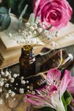 Spring flowers pink roses and white gypsophila. Vintage books and brown bottles stock photos