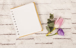 Spring flowers: pink tulip and lilac eustoma near notebook Royalty Free Stock Photo