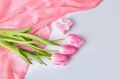 Pink tulips bouquet with gift box on a table royalty free stock image