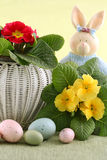 Spring flowers. Pretty red and yellow primulas inside white woven wicker basket with pastel speckled Easter eggs and a whimsical bunny peeking from behind Stock Photo