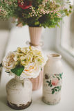 Spring flowers in retro vases on windowsill Royalty Free Stock Images