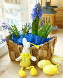 Spring flowers in a small basket and easter rabbit. With easter eggs on the window of balcony Royalty Free Stock Photography