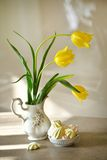 Spring flowers still life. Fresh yellow tulips bouquet in vase. Meringue cookies Royalty Free Stock Photography