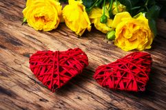 Spring flowers and symbolic red hearts. Bouquet of yellow roses and symbolic red hearts.Postcard for Valentine Day Royalty Free Stock Image