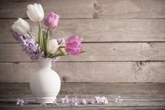Spring flowers in vase on old wooden background. The spring flowers in vase on old wooden background Royalty Free Stock Photo