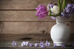 Spring flowers in vase on old wooden background. The spring flowers in vase on old wooden background Stock Image