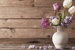 Spring flowers in vase on old wooden background. The spring flowers in vase on old wooden background Royalty Free Stock Photos