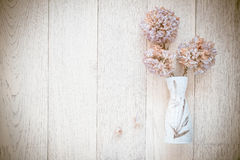 Spring flowers in vase on table on white wooden background. Stock Photos