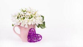 Spring flowers and wicker heart. Copy space stock photo