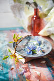 Spring flowers on wooden dish set with a book near a window Royalty Free Stock Photo