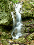 Spring flowing down rocks. Details of picturesque natural spring cascading down rocks with slow motion blur effect Stock Photography