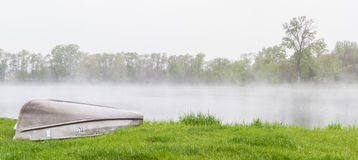 Spring fog over the lake. Early morning fog lingering over the lake with vivid green trees surrounding it and a small fishing boat Stock Photography