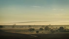 Spring foggy dawn in the steppe. Panorama of a wide valley stock photography