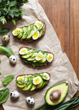 Spring food. Sandwiches with avocado, spinach, guacamole and quail eggs on parchment. Low carbohydrate diet of organic Stock Photography