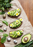 Spring food. A whole grain bread toast sandwiches with avocado, spinach, guacamole, arugula and quail eggs on parchment Stock Photography