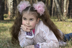Spring in the forest girl with long hair with a large bow. Royalty Free Stock Images