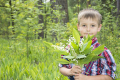 Spring in the forest little boy  holding a small bouquet lily of Royalty Free Stock Photography