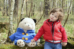Spring in the forest little girl playing with a toy bear. Stock Photos