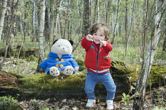 Spring in the forest little girl playing with a toy bear. Stock Photography