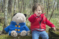 Spring in the forest little girl playing with a toy bear. Stock Image