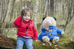 Spring in the forest little girl playing with a toy bear. Stock Images