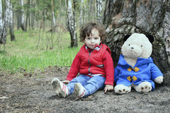 Spring in the forest little girl playing with a toy bear. Stock Photo