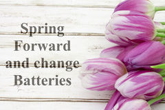 Spring Forward message. A bouquet of purple tulips on weathered wood with text Spring Forward and change Batteries royalty free stock photos