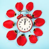 Spring forward time. Stylish vintage red alarm clock. Daylight savings time concept. Alarm clock with tulip petals around. Flat. Lay style, over blue background royalty free stock photography