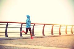 Spring för idrottsman nen för konditionkvinnalöpare på sjösidavägen Fotografering för Bildbyråer