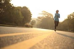 Spring för idrottsman nen för konditionkvinnalöpare på vägen Arkivfoton