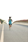 Spring för konditionkvinnalöpare på vägen Royaltyfri Bild