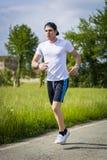 Spring för ung man och jogga på vägen i land Arkivfoto