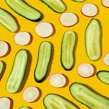 Dietary vegan food - freshly picked vegetables cocumber and radish as a geometric pattern on a yellow background. Flat stock photos