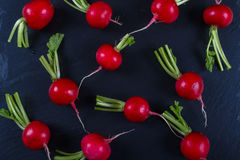 Spring fresh radishes background on the black slate board. Top view Stock Photo