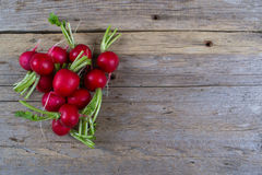 Spring fresh radishes background. On a old wooden table Stock Photo