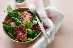 Spring fresh salad with blood orange, lettuce, spinach and sesame seeds on pink background. Top view. Selective focus royalty free stock photos